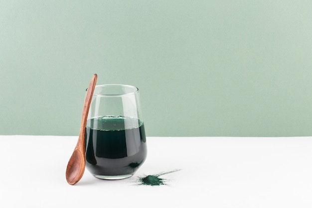 Spirulina drink in a glass on a white table, green space, minimalism