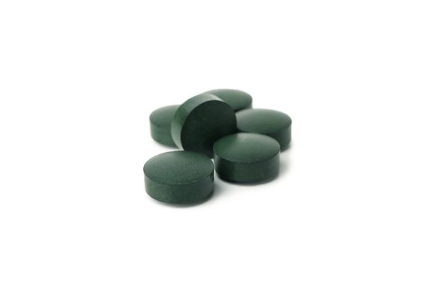 Спирулина в таблетках, изолированные на белом фоне