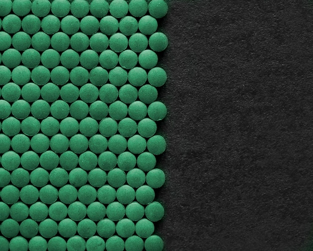 Spirulina pills on black background. green tablets superfood. flat lay, top view, copy space