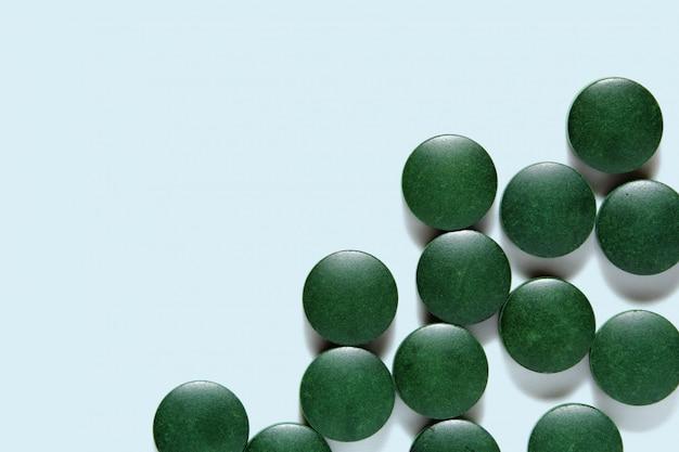 Spirulina pills, green tablets on blue surface