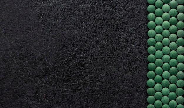 검은 배경에 스피루리나 알약입니다. 녹색 정제 슈퍼 푸드. 평평한 평지, 평면도, 복사 공간