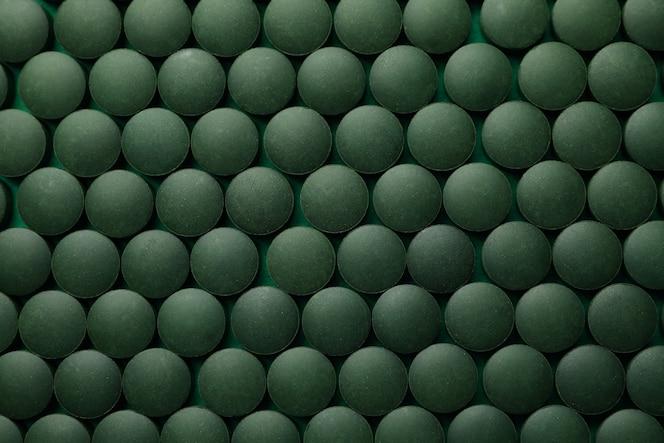 spirulina in pillole su sfondo intero, vista dall'alto