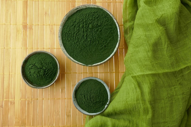 Spirulina powder in cups set and green scarf on bamboo mat