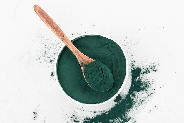 Spirulina powder in a white bowl with spoon