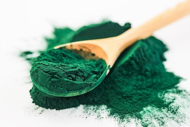 Spirulina powder in a wooden spoon