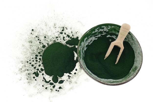 Водоросли spirulina. порошок спирулины в керамической зеленой чашке с деревянным шариком, изолированной на белом фоне.