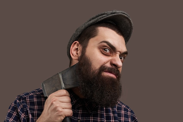 Spiteful brutal bearded man shave by axe. portrait of hipster with beard. hot-tempered male concept. crazy emotion on face.