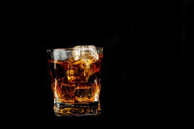 Брызги алкогольного напитка виски со льдом с каплями в стакане