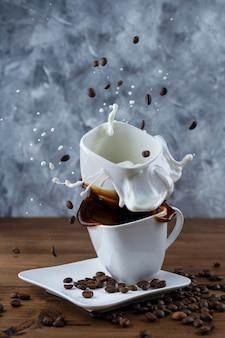 커피가 든 머그에 있는 설탕 조각과 나무 배경에 우유가 든 머그를 튀기고 튀깁니다.