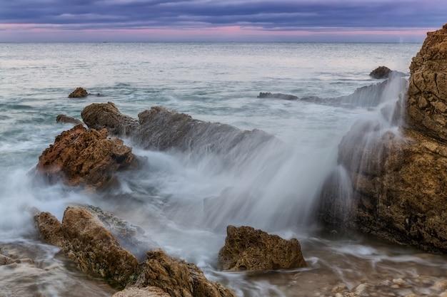 岩に対する波のしぶきとスプレー。海に沈む夕日。