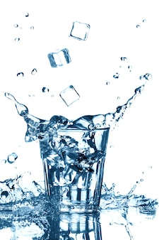 Splash of clean water with flying ice cubes in glass on white. isolated. healthy lifestyle.
