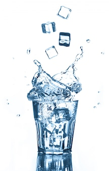 Splash of clean water with flying ice cubes in glass on white. isolated.