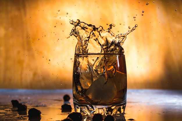 Splash of cold ice in glass of whiskey