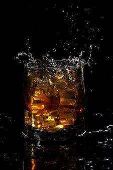 黒の背景に氷とスコッチウイスキーのガラスからスプラッシュ