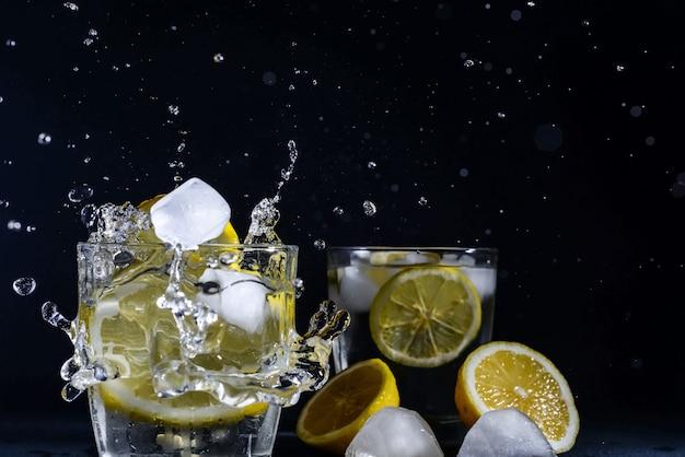 Джин с тоником коктейль с ломтиками лимона кубик льда падает в воду с лимоном копия пространство, лимонад