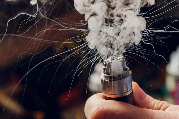 Разбрызгайте глицерин на вейп-спираль. большие облака тумана с видимыми трассерами. вейп-культура и отказ от курения.