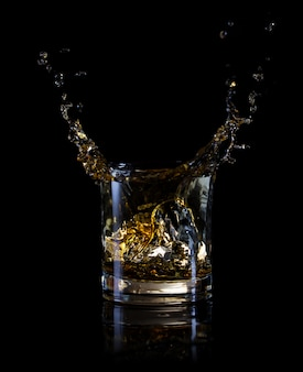 Splash of ice in a glass of whiskey