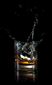 Splash of ice in glass of whiskey