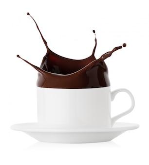 Всплеск черного шоколада в белой чашке и блюдце