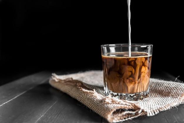 Всплеск ледяного кофейного напитка на коричневом фоне. чашка с кубиками льда. волна холодных напитков. макро дизайн ликер молока, кофе и льда. сливки наливаются в чашку