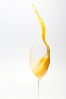 Всплеск апельсинового сока в стакане на белой поверхности