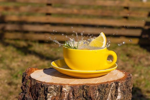 Всплеск чая в желтой чашке с лимоном на деревянном бревне во дворе