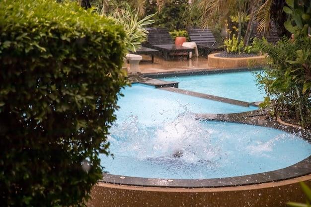 降り注ぐ雨の中で熱帯の屋外プールに飛び込んだ後の水のしぶき