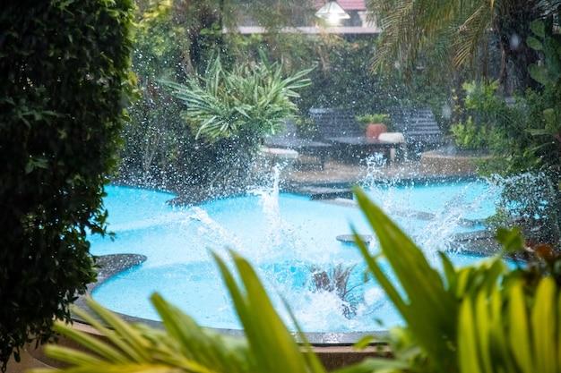 降りしきる雨の中、熱帯の屋外プールに飛び込んだ後の水のしぶき