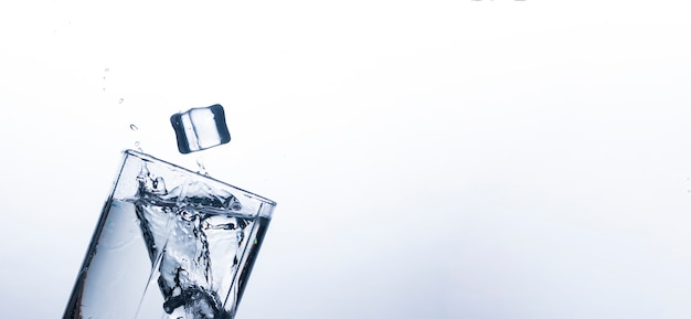 Splash of water in a glass from an ice cube . concept of quenching thirst and cooling drinks in hot weather. water balance and daily water consumption. .