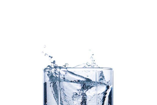 Splash of water in a glass from an ice cube .