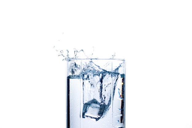 A splash of water in a glass from an ice cube . the