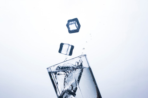 A splash of water in a glass from an ice cube .