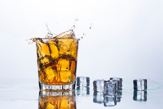 A splash of whiskey from ice cubes . concept of alcoholic drinks with ice, whiskey or brandy, apple juice and cooling drinks.