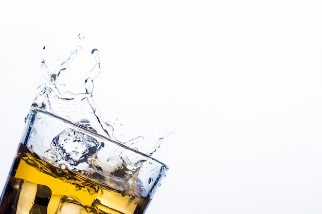 Splash of whiskey from ice cubes . concept of alcoholic drinks with ice, whiskey or brandy, apple juice and cooling drinks.