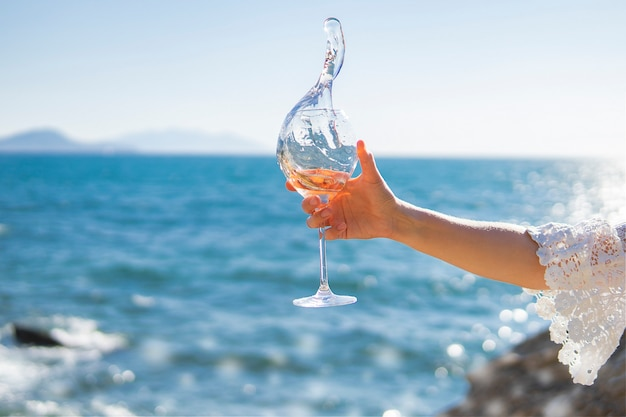 Splash of wine. hand holding glass of rose vine on sea or ocean background.