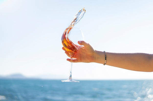 Splash of wine. hand holding glass of rose vine on sea or ocean background.