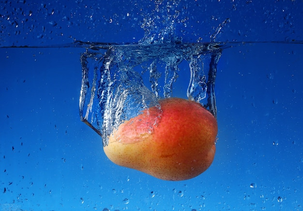 Splash with pear on a blue wall