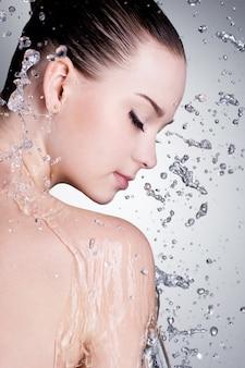 Schizzi e gocce d'acqua intorno al viso femminile con pelle pulita - verticale