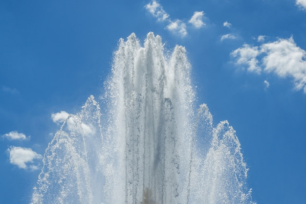 Splashes of the fountain against the blue sky