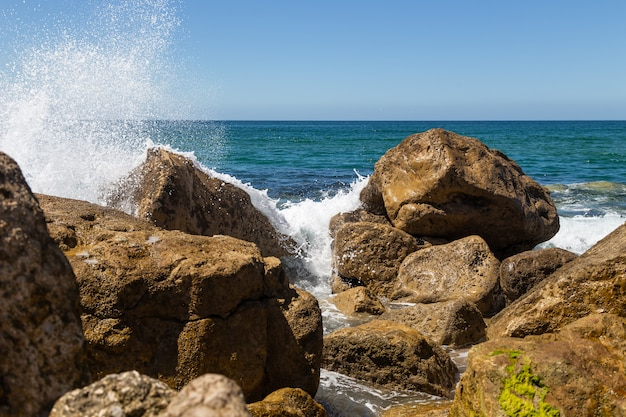 Splashes from a wave on the rocks in sunny day