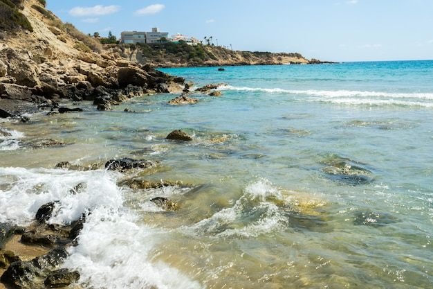 Брызги морской воды разбиваются о прибрежные скалы