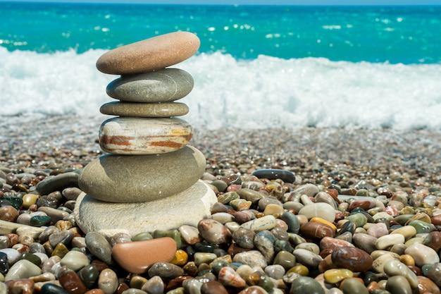 沿岸の岩に砕ける水の飛沫が滑らかな海の石