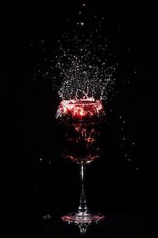 クリスタルグラスの周りにワインが飛ぶ