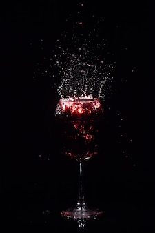 Splashes of red juice fly around crystal wineglass standing in dark space