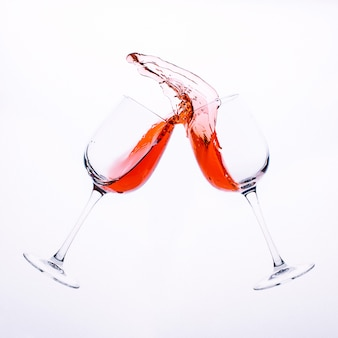 Splashes of red wine from two clear glass glasses isolated on a white surface