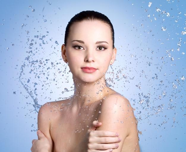 Spruzzi d'acqua sulla bella giovane donna con la pelle fresca e pulita - sfondo colorato