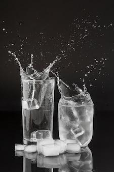 Spruzzi d'acqua in bicchieri trasparenti