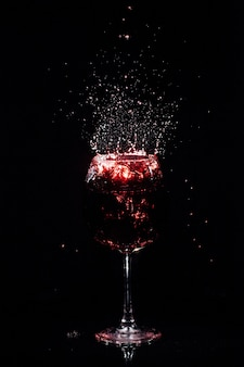 Splashes of wine fly around crystal glass