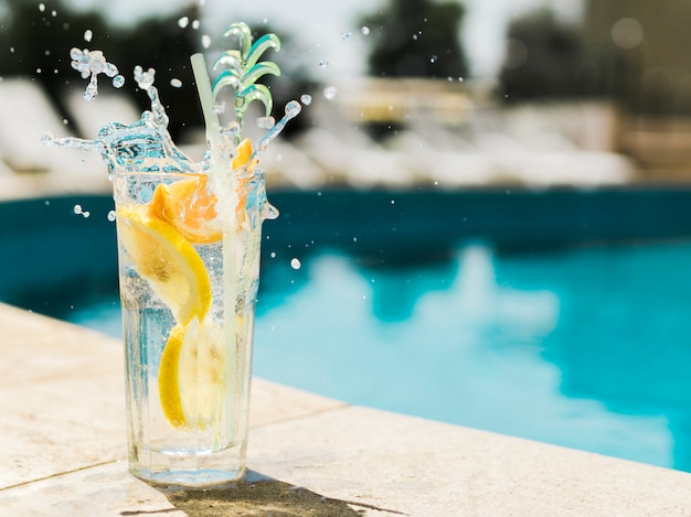 Splashing cocktail with lemon near pool