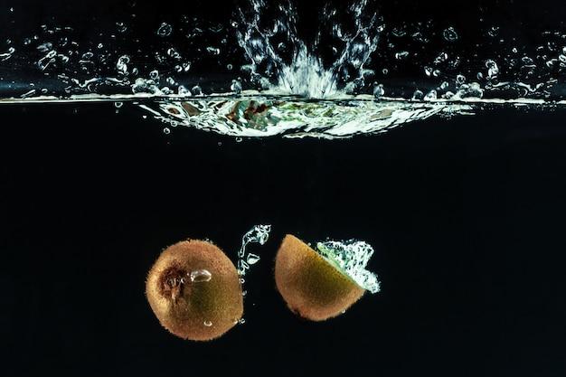 Splashing kiwi fruit on the water